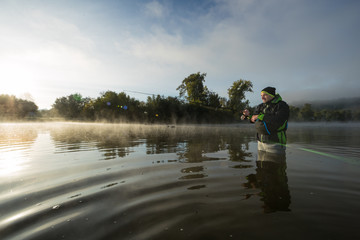 Printed kitchen splashbacks Fishing Man fishing in river with fly rod during summer morning.