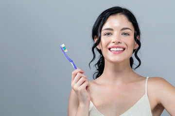 Young woman holding a toothbrush on a gray background
