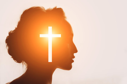 Symbol of Christianity concept. Woman silhouette and the Cross.