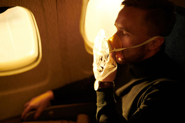 Side view portrait of mature man wearing oxygen mask in plane, copy space