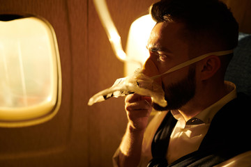 Side view portrait of handsome young man wearing oxygen mask in plane, copy pace