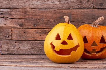Two funny Halloween pumpkins on wooden boards. Halloween pumpkins with happy faces. Symbol of traditional autumn holiday.