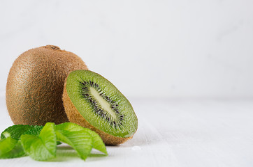 Ripe green kiwi with half cut and juice drop flow down and young leaves closeup on white wood board as fresh summer fruits background.