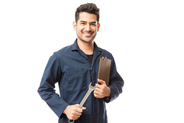 Smiling Male Repairman Holding Wrench And Clipboard