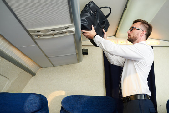 Waist up  portrait of handsome businessman taking leather bag from luggage compartment in plane, copy space