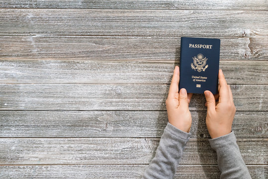 Person holding a US passport on a wooden desk from above
