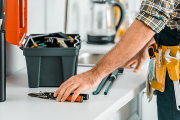 cropped image of plumber putting tools on kitchen counter in kitchen Wall mural