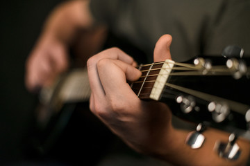 hands play on acoustic guitar
