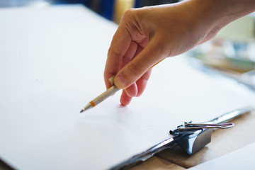 Artist with a pencil close-up while drawing a sketch on clean paper.