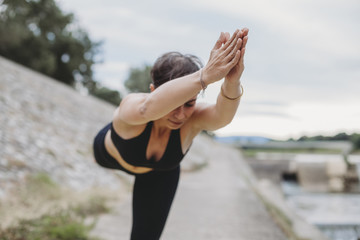 Young beautiful woman doing yoga exercises in park on the bank river in summer