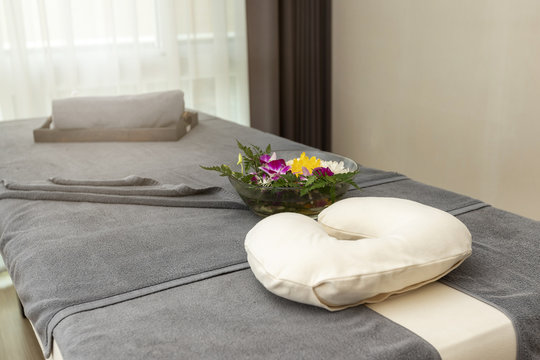 Pillow with Towel and flower on massage table in modern spa salon