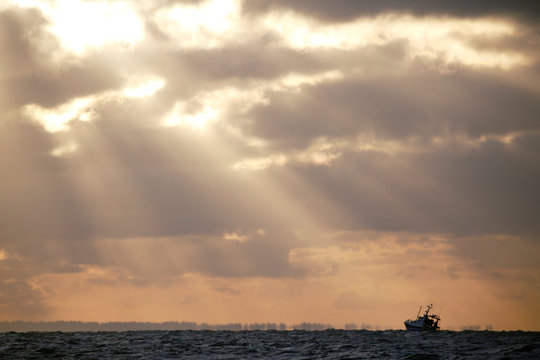 A French trawler is seen fishing during sunset at the start of the scallop fishing season off Port-en-Bessin