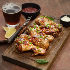 Roasted chicken drumsticks with sesame on a cutting board on a wooden background
