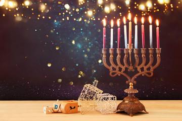 image of jewish holiday Hanukkah background with menorah (traditional candelabra) and burning candles.