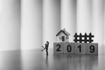 Miniature people, husband and wife hug each other on year 2019 background using as family concept - Black and white filter