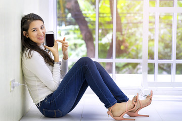 Young attractive woman sitting on floor  while charging smart phone, feeling happiness when showing her pictures on camera phone record. Impress photos Images from professional Photographer.