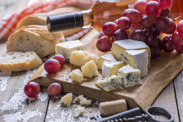 The bottle of rose wine with cheese, white bread, fresh grape on a wooden board, background.