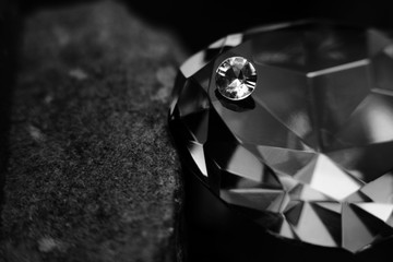 A Single Diamond on Top of a Large Gem Stone, Showing the Facet Cut of the Jewel.