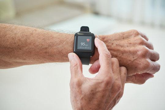 Senior man checking pulse via health application in his smart watch