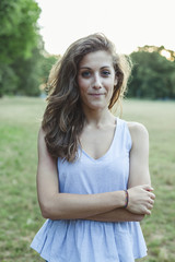 Portrait of beautiful young woman in park at sunset during summer