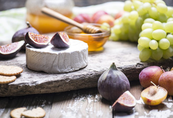 The set of natural products - soft cheese, figs, grape, plums, honey with stick on a wooden board.
