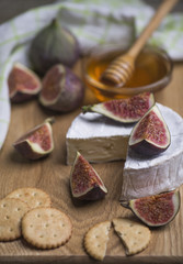 Ripe fresh figs, cheese, cracker with honey in a glass bowl on a wooden board.