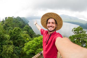 Handsome traveller man taking a selfie smiling on the camera on a nature landscape