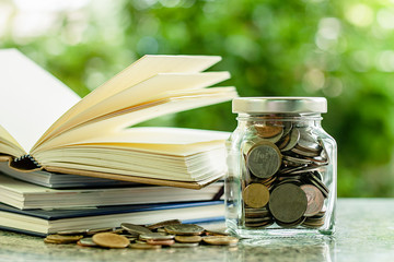 Money coins in the glass jar with stack of opened books against blurred natural green background for save money and education financial concept