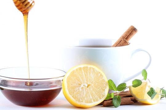корица , лимон, чай  мёд лежат на белом фоне