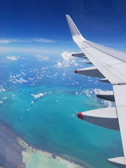 Airplane wing view above the Caribbean sea.