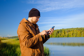 young bearded man in hat on the background of the lake looking into the phone