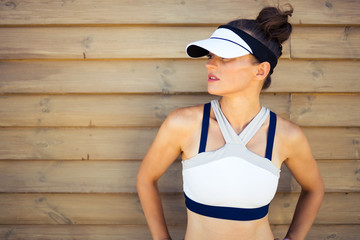 fit woman jogger looking aside against wooden wall