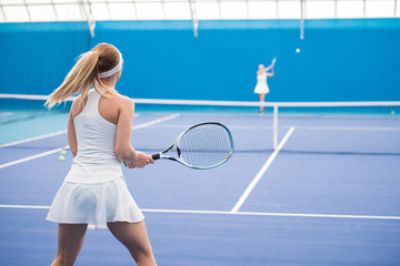 Back view portrait of female tennis player holding racket during training in indoor court, copy space