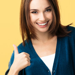 young woman showing thumbs up gesture, over yellow