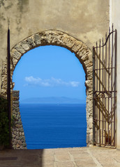Open gate showing a marvelous view on the mediterranean sea, blue sky and blue ocean, Cala Spinosa, Sardinia, Italy
