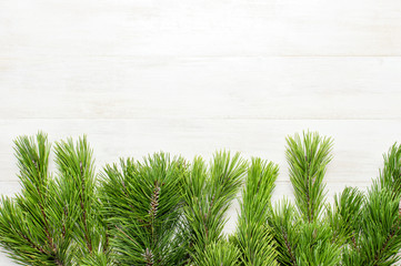 Christmas background, green pine branches on white wooden table. Creative composition with border and copy space design top view. New Year's, holiday, christmas, decoration