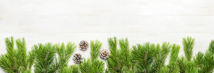 Christmas background, green pine branches, cones decorated with snow on white wooden table. Creative composition with border and copy space design top view. New Year's, holiday, long banner