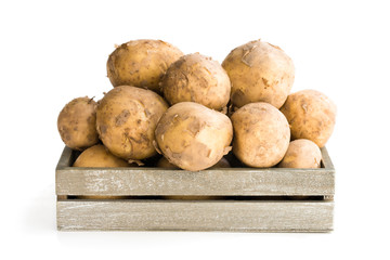 New potatoes  in wooden box isolated on white