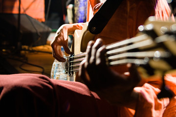 Playing the 4-string guitar. Close-up view of the playing on a concert