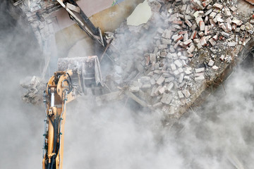 Building demolition with an excavator in dust cloud.