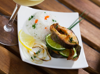 Tasty baked trout steaks, served at plate with rice and lemon, glass of wine