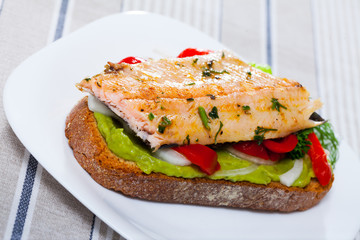 Delicious sandwich with trout,  guacamole and fresh pepper at plate
