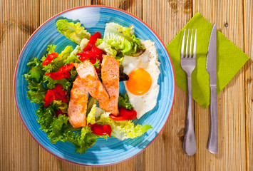 Tasty breakfast with  trout, egg, pepper and lettuce at plate on table