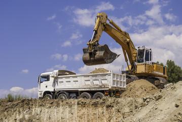 Excavator loads dump truck soil on the construction site