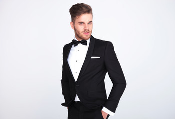 attractive man in black tuxedo standing with hands in pockets