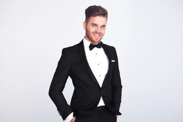 portrait of relaxed smiling gentleman in black tuxedo standing
