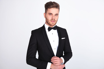 portrait of young man in black tuxedo fixing his links
