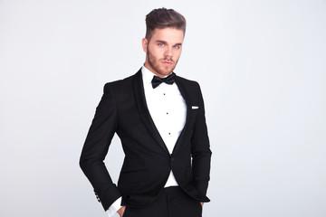 portrait of relaxed man in black tuxedo standing
