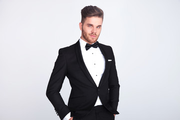 smiling man in black tuxedo standing with hands in pockets