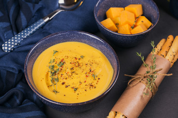 Pumpkin soup in blue bowl topped with fresh herb